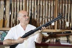 Propriétaire de magasin mûr d'arme à feu regardant l'arme dans la boutique Image stock