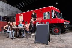 Propriétaires heureux au camion de nourriture Photographie stock libre de droits