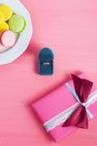 Propuesta de matrimonio, caja con un anillo, macarrones y regalo en fondo rosado El foco selectivo, visión superior, macro, enton Imagenes de archivo