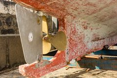 Propulseur et gouvernail de direction d'un vieux bateau de pêche en détail image stock