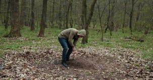 Гай устанавливает домодельный крест на могиле мертвого любимца Похороны собаки, могила с крестом Близко вверх Prores, замедленное сток-видео