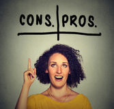 Pros and cons argument concept. Woman with glasses looking up deciding Stock Photo
