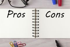 Pros and Cons written in notebook. Pros and Cons List written in notebook on wooden desk with marker pen and glasses. Top view Stock Photos