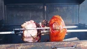 Prosciutti deliziosi della carne di maiale arrostiti su fuoco Alimento della via a Praga stock footage