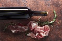Prosciutto με το δεντρολίβανο και το μπουκάλι του κόκκινου κρασιού Στοκ εικόνα με δικαίωμα ελεύθερης χρήσης