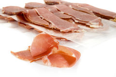 Prosciutto. Slice of prosciutto with more slices in background Stock Photos
