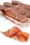 Prosciutto. Slice of prosciutto with more slices in background Stock Photo