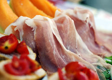 Prosciutto. Photo of prosciutto, Italian cured ham, with tomato, melon, and cheese Royalty Free Stock Photos
