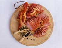 Prosciutto affumicato, rosmarini secchi del pepe nero interi e sul piatto di legno Immagini Stock