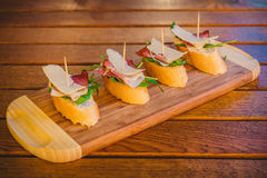 Prosciutto appetizers. On a wooden plate and table Royalty Free Stock Images