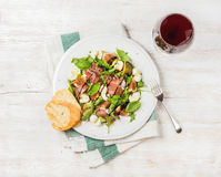 Prosciutto, Arugula, Basilikum, Feigen Salat und Glas Rotwein Stockbilder