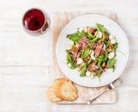 Prosciutto, Arugula, Feigensalat mit Stangenbrotscheiben und Wein Stockfotografie