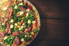 Prosciutto arugula pizza on brown wooden background stock photography