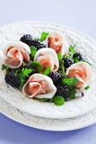 Prosciutto and blackberries salad. Prosciutto, blackberries and green salad on the plate, selective focus Royalty Free Stock Photography