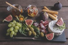 Prosciutto ,camembert cheese, figs,honey, grapes, olives on dark serving board over rustic wooden background Stock Photo