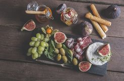 Prosciutto ,camembert cheese, figs,honey, grapes, olives on dark serving board over rustic wooden background Royalty Free Stock Images