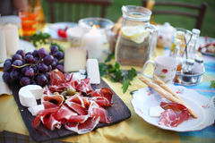 Prosciutto with cheese and grapes on a picnic table Stock Photos