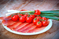 Prosciutto, cherry tomatoes and onion Stock Image