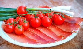 Prosciutto, cherry tomatoes and onion on plate Royalty Free Stock Photo