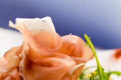 Prosciutto close up on blue background Royalty Free Stock Photos