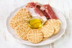 Prosciutto con las tostadas y el aceite de oliva Imagen de archivo libre de regalías