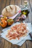 Prosciutto con pane, il pomodoro, l'aglio e l'olio d'oliva fotografia stock libera da diritti