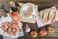 Prosciutto con pane, il pomodoro, l'aglio e l'olio d'oliva immagini stock