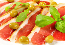 Prosciutto crudo with green olives Stock Images