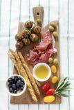 Prosciutto crudo mięśni i Stubarwni pomidory zieleń i blac, zdjęcie royalty free