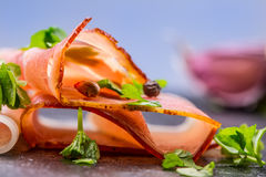 Prosciutto. Curled Slices of Delicious Prosciutto with parsley leaves on granite board. Prosciuto with spice cherry tomatoes garli Stock Photo