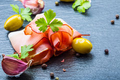 Prosciutto. Curled Slices of Delicious Prosciutto with parsley leaves on granite board. Prosciuto with spice cherry tomatoes garli Royalty Free Stock Photos