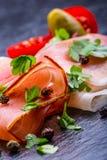 Prosciutto. Curled Slices of Delicious Prosciutto with parsley leaves on granite board. Prosciuto with spice cherry tomatoes garli Stock Photo