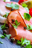 Prosciutto. Curled Slices of Delicious Prosciutto with parsley leaves on granite board. Prosciuto with spice cherry tomatoes garli Stock Photography