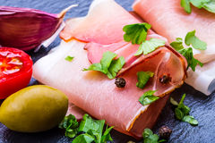 Prosciutto. Curled Slices of Delicious Prosciutto with parsley leaves on granite board. Prosciuto with spice cherry tomatoes garli Royalty Free Stock Photo