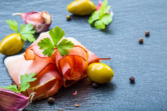Prosciutto. Curled Slices of Delicious Prosciutto with parsley leaves on granite board. Prosciuto with spice cherry tomatoes garli Royalty Free Stock Image