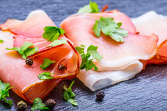 Prosciutto. Curled Slices of Delicious Prosciutto with parsley leaves on granite board. Prosciuto with spice cherry tomatoes garli Stock Images