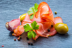 Prosciutto. Curled Slices of Delicious Prosciutto with parsley leaves on granite board. Prosciuto with spice cherry tomatoes garli Stock Image