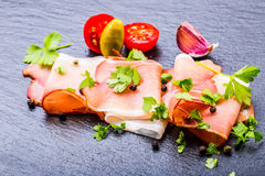 Prosciutto. Curled Slices of Delicious Prosciutto with parsley leaves on granite board. Prosciuto with spice cherry tomatoes garli Royalty Free Stock Photography