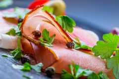 Prosciutto. Curled Slices of Delicious Prosciutto with parsley leaves on granite board. Prosciuto with spice cherry tomatoes garli Royalty Free Stock Images