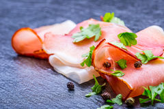 Prosciutto. Curled Slices of Delicious Prosciutto with parsley leaves on granite board. Prosciuto with spice cherry tomatoes garli Stock Photos