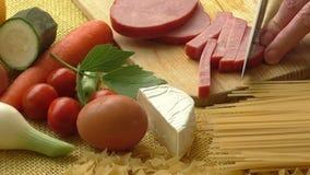 Prosciutto della carne di maiale su un tagliere di legno con gli ortaggi freschi video d archivio