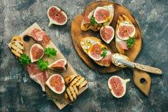 Prosciutto di Parma con i fichi Fichi freschi con il prosciutto ed il formaggio su un pane tostato arrostito, fondo rustico Spunt immagini stock
