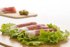 Prosciutto di Parma ham and leaf of salad 2. Prosciutto di Parma ham and leaf of salad in the back green olive on the wooden plate Stock Image