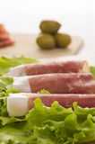 Prosciutto di Parma ham and leaf of salad closeup. Prosciutto di Parma ham and leaf of salad in the back green olive on the wooden plate closeup Royalty Free Stock Image