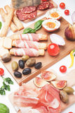 Prosciutto di Parma and other italian food. Prosciutto di Parma with olives and other italian antipasto food Stock Photo
