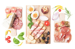 Prosciutto di Parma and other italian food. Prosciutto di Parma with olives and other italian antipasto food isolated on white background Stock Photo