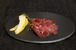 Prosciutto di prosciutto di Parma affettato, fondo di legno, rosmarino Immagini Stock Libere da Diritti