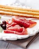 Prosciutto di Serrano con il grissini e le olive Fotografie Stock