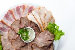 Prosciutto e bacon affumicati differenti con lattuga su fondo bianco Immagine Stock