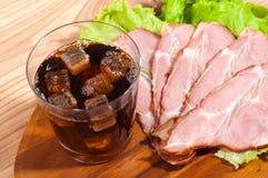 Prosciutto e lattuga con vetro di una cola su un piatto di legno immagini stock libere da diritti
